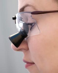 Zahnärztin arbeitet mit Lupenbrille